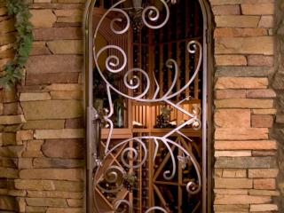 Custom Wood Wine Racks shown through Custom Wine Room Iron Door