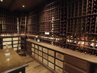 Dark Wooden Wine Racks in Dim Lit Custom Built Wine Cellar by Innovative Wine Cellar Designs