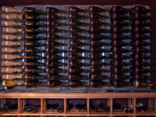 Metal Wine Racks Mounted to Wall with Wood Wine Shelves Beneath.
