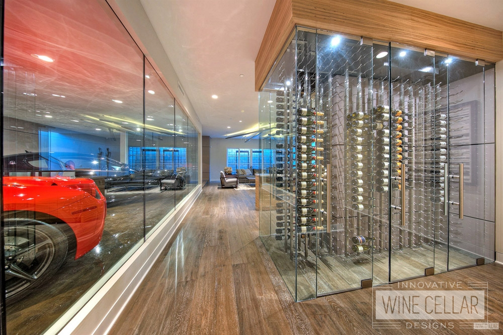 Contemporary wine cellar at car dealership featuring glass doors, wood & stainless steel accents.