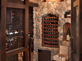 Stone & brick wine cellar with reclaimed wine barrel racking, custom design & install by Innovative Wine Cellar Designs.