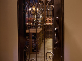 Custom Wine Cellar Door Design with Scrolled Wrought Iron Accents - By Innovative Wine Cellar Designs