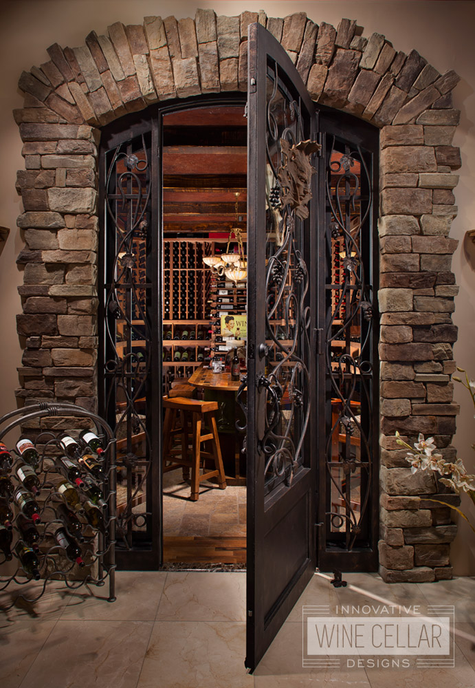 wrought iron door in stone arch entryway into wine cellar