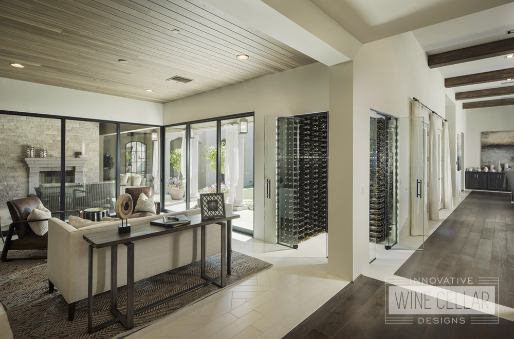 Dual sided entry wine cellar with glass doors and walls to match rustic contemporary decor.