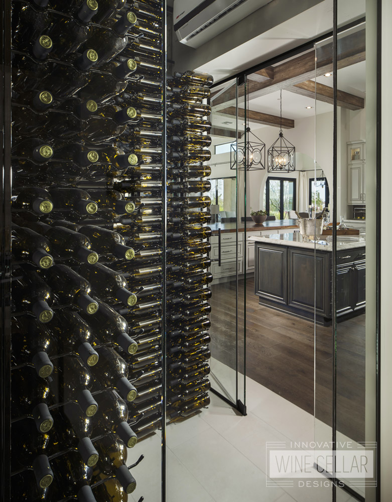Dual entry wine cellar with glass doors and walls to match rustic contemporary decor.