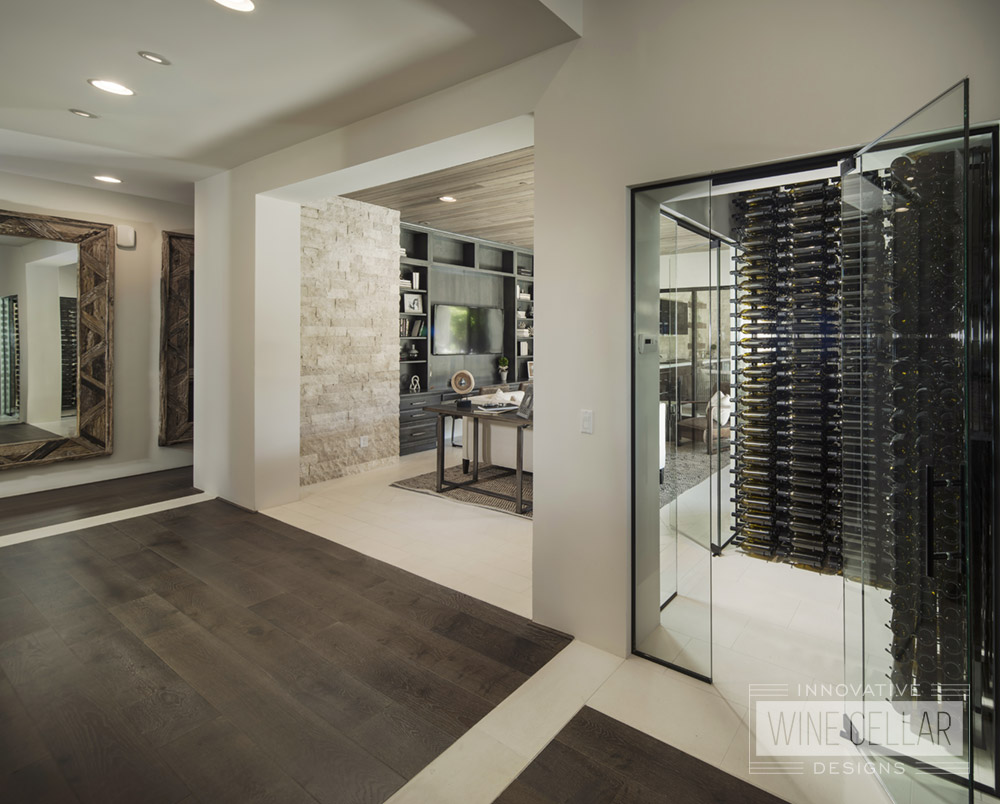 Dual entry wine cellar with glass doors and walls to match contemporary decor.