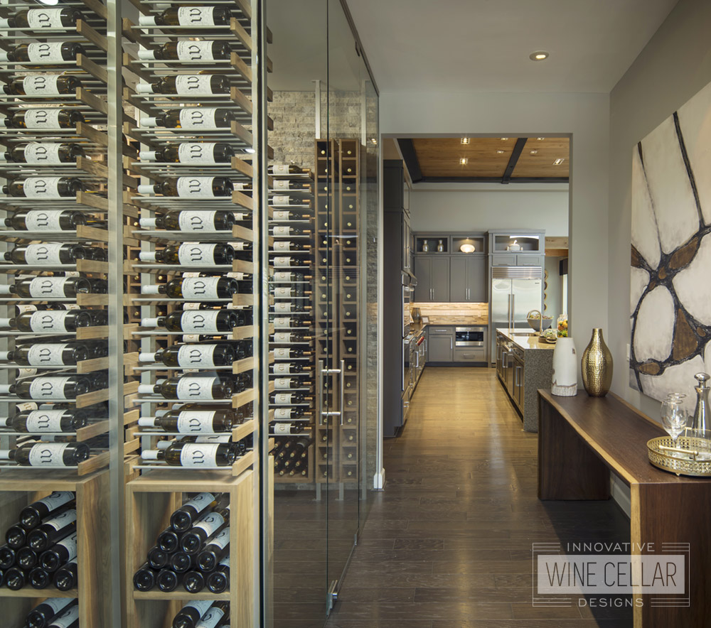 Wine cellar with glass facing door to hallway that leads to kitchen area.