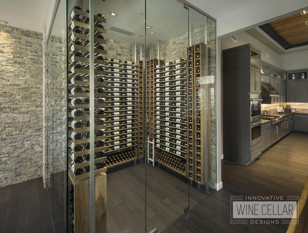 Corner room wine cellar with glass facing walls and wood racks with stone style back walls.