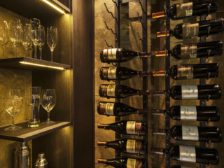 Wine cellar room with metal wine racks and dim lighting to match contemporary decor.
