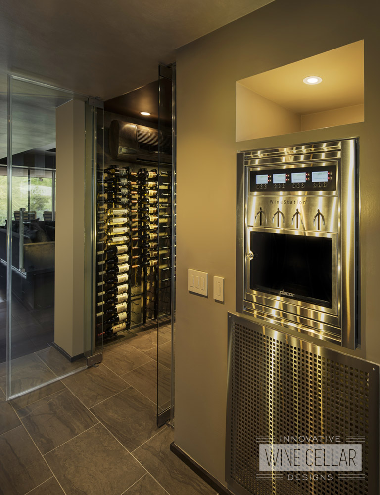 Contemporary wine room designed with glass doors and metal racking to match sleek kitchen appliances.