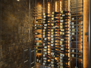 Wine cellar room with mixed metal and wood racking and accent back and ceiling lighting.