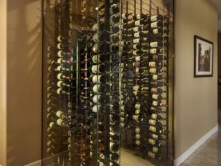 Contemporary style corner wall wine storage room with glass facing walls and metal wine racks.