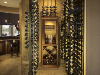 Contemporary style wine closet with glass walls and door with metal wall mounted wine racks.