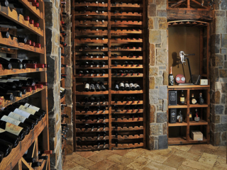 Under stairs custom wine cellar using reclaimed wine barrels & antique decor, created by Innovative Wine Cellar Designs.