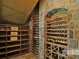 Under stairs custom wine cellar using reclaimed wine barrels, created by Innovative Wine Cellar Designs.