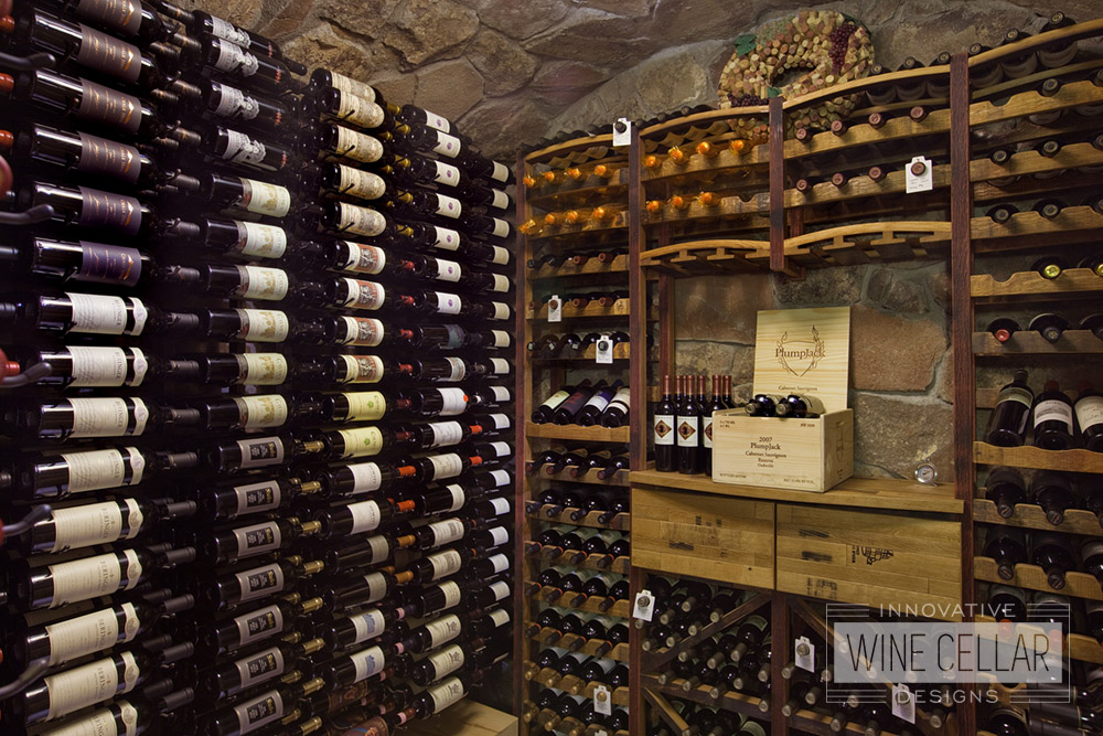 Rustic stone wine cellar & reclaimed wine barrel racking, created by Innovative Wine Cellar Designs.