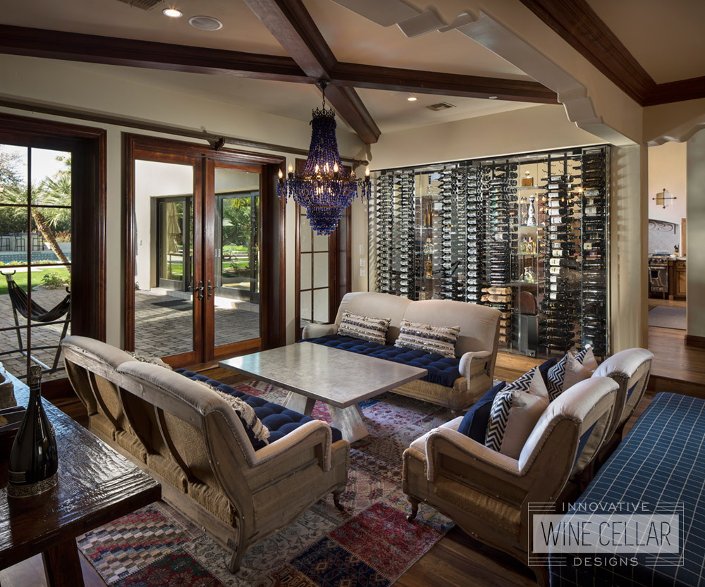 This glass wine wall cellar transforms the look of this cozy living room area, allowing light to pass through from the kitchen.