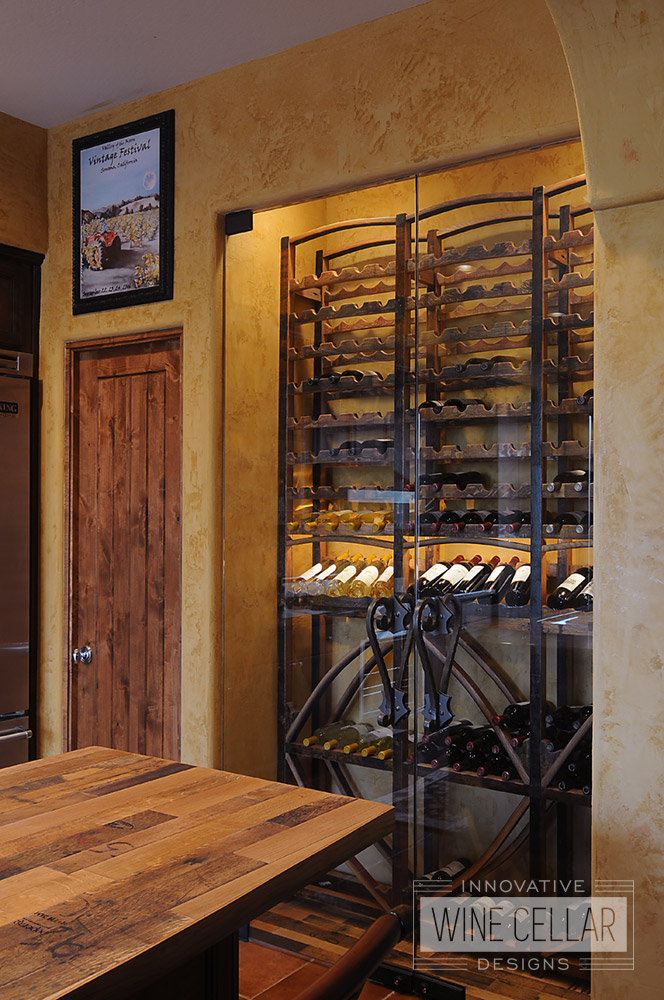 Reclaimed wine barrel racking in recessed glass wine cellar