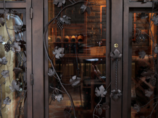 Custom Glass Wine Cellar Door Design with Wrought Iron Archway and Grape Vine Accents by Innovative Wine Cellar Designs.