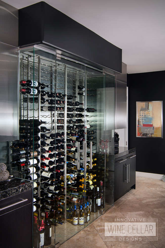 Modern kitchen glass wine cellar, custom design & install by Innovative Wine Cellar Designs.