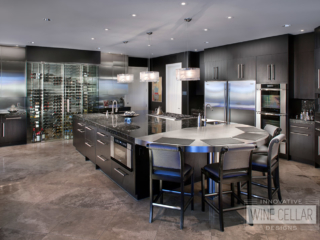 Recessed glass wine cellar in kitchen wall with stainless steel accents matching modern appliances.