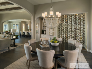 Recessed glass wall wine storage storage room located in contemporary styled dining room area.