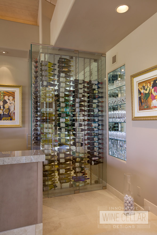 Custom glass wine cellar built to fit in small corner of wet bar area and designed to match modern decor.